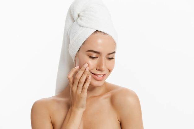 A rapariga feliz com pele limpa e com uma toalha branca em sua cabeça lava a face.