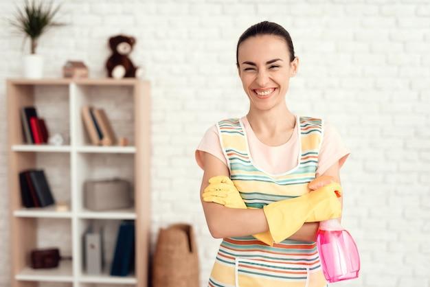 A rapariga limpa a casa com os detergentes.