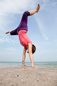 A rapariga mostra um acrobático na praia.