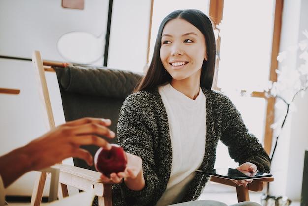 A rapariga no escritório dá a apple ao colega