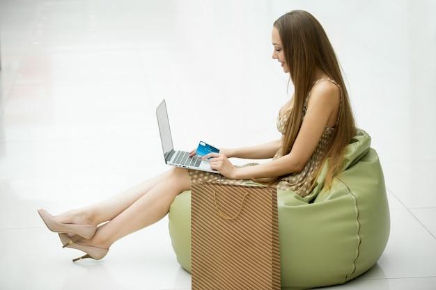 A rapariga senta-se em um saco de feijão com um laptop