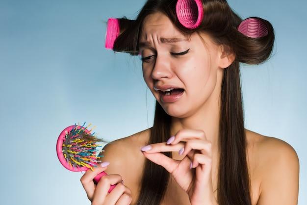 A rapariga triste perde o cabelo, continua a pentear, grandes rolos de cabelo na cabeça