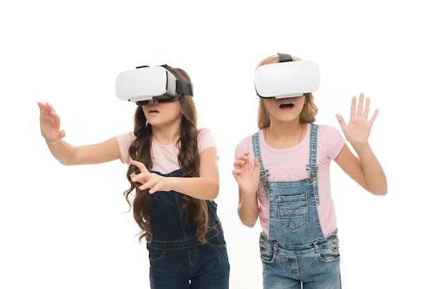 A realidade virtual é emocionante. meninas crianças usam óculos de fundo branco de vr. conceito de educação virtual. vida moderna. interação em espaço virtual. jogos cibernéticos. tecnologia de realidade aumentada.