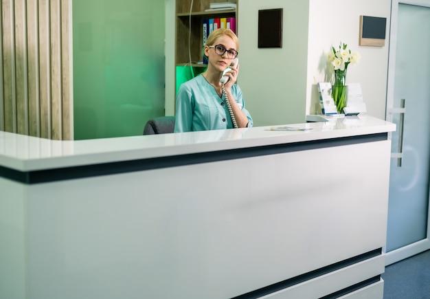 A recepcionista do hospital atende o telefonema. processo de trabalho. sala de espera moderna com balcão de recepção. área de recepção.