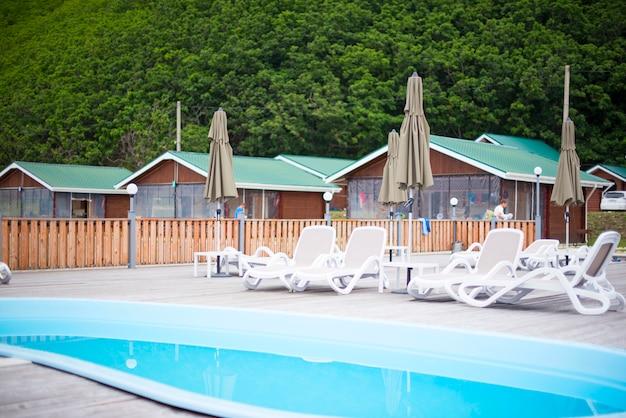 A recreação da recreação do clube de país relaxa o guarda-chuva de madeira do lounger do sol das árvores de floresta da casa da associação.
