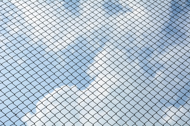 A rede de metal de gaiola no fundo do céu azul - padrão de estilo