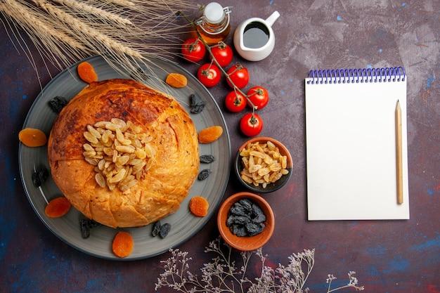 A refeição oriental do shakh plov, vista de cima, consiste em arroz cozido dentro de uma massa redonda em um fundo escuro.