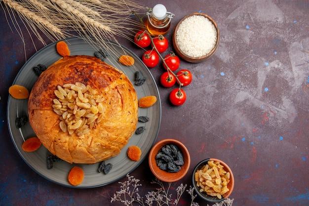 A refeição oriental do shakh plov, vista de cima, consiste em arroz cozido dentro de uma massa redonda em uma massa de refeição culinária de fundo escuro