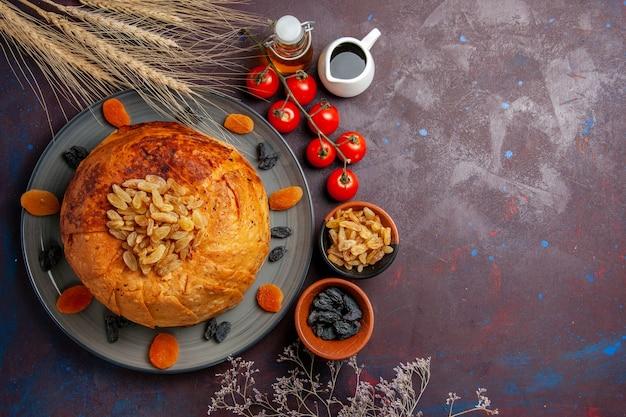 A refeição oriental do shakh plov, vista de cima, consiste em arroz cozido dentro de uma massa redonda em uma mesa escura.
