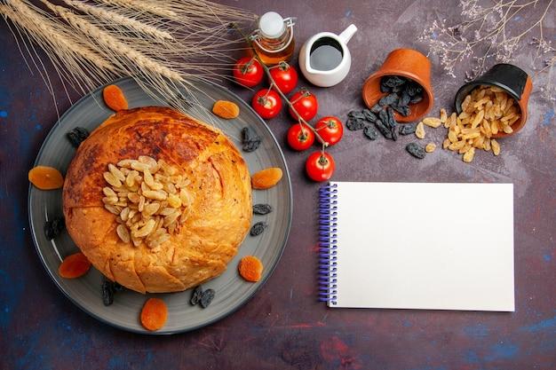 A refeição oriental do shakh plov, vista de cima, consiste em arroz cozido dentro de uma massa redonda no fundo escuro.