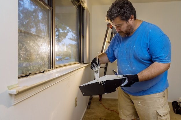A reforma da casa no trabalhador braçal pinta com uma camada de pincel de cor branca uma moldura de janela