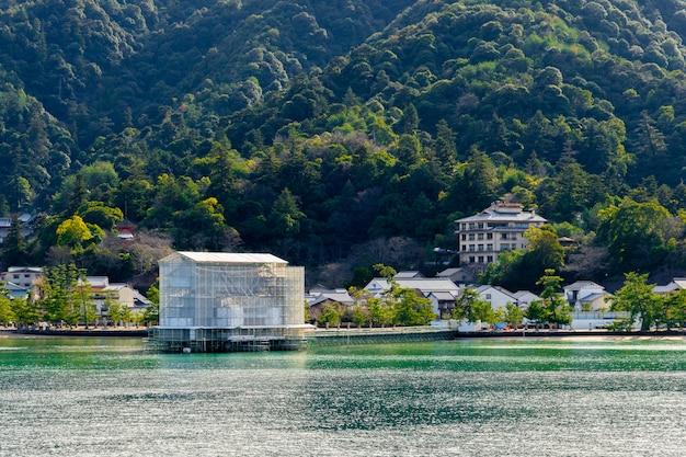 A reforma funciona no famoso portão torii flutuante de miyajima. durante as obras de renovação, o portão torii é coberto por andaimes transparentes