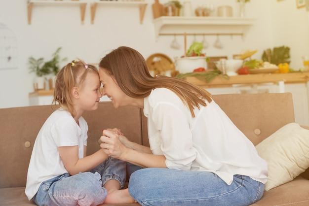 A relação de confiança entre mãe e filha. conversa de uma mulher com uma menina em casa no sofá da cozinha. melhores amigos, fim de semana de maternidade feliz junto com o conceito de criança.