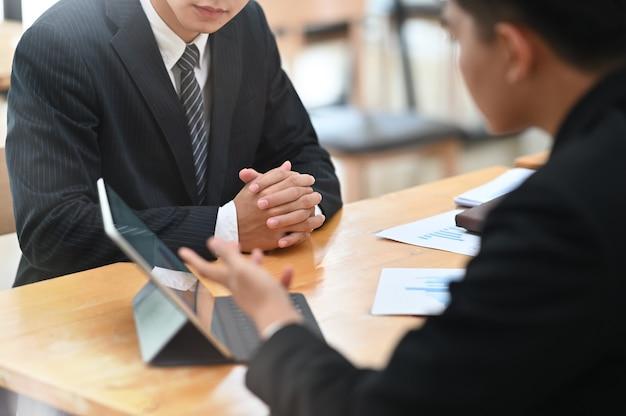 A reunião de dois homens de negócios e consulta com o computador portátil digital na tabela.