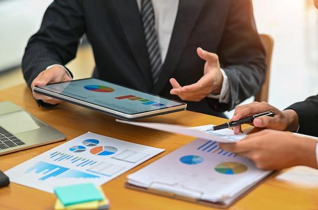 A reunião de negócios com tabuleta digital, consulta o conceito.