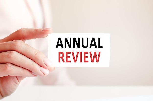 A revisão anual é escrita em um cartão de visita branco, escrito por uma mulher.