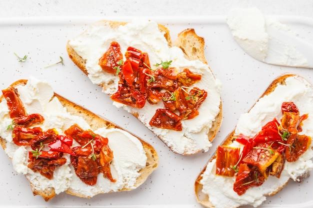 A ricota e o sol secaram sanduíches dos tomates na placa branca.