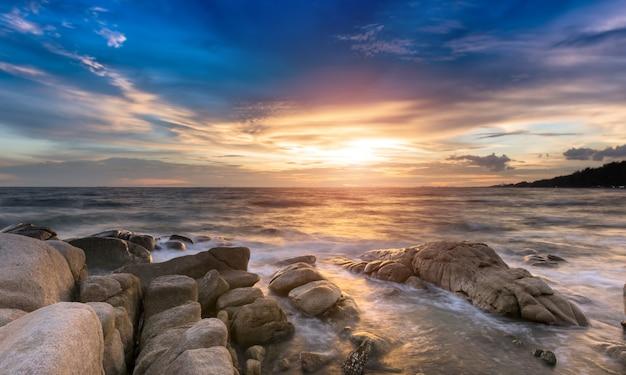A rocha e o mar na cor da hora do pôr do sol.