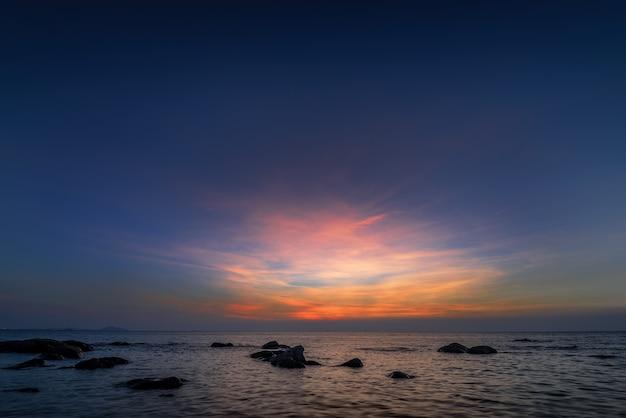 A rocha no mar com o céu do sol
