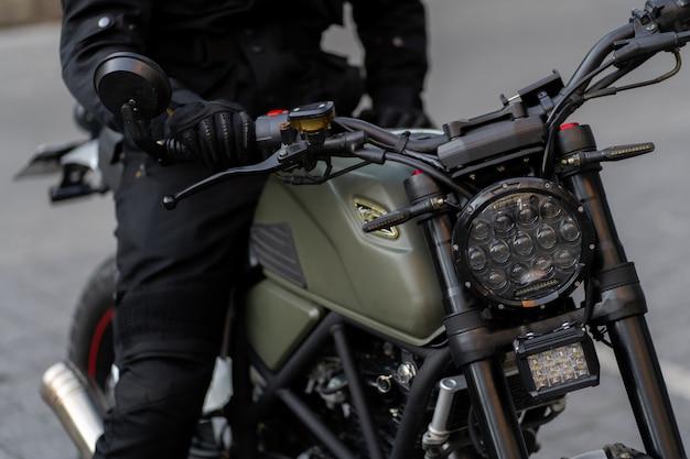 A roda dianteira da motocicleta com um freio a tambor e um cabo para ela é o garfo dianteiro com um amortecedor absorvido e uma mola. foco em um farol. moto retro com farol.