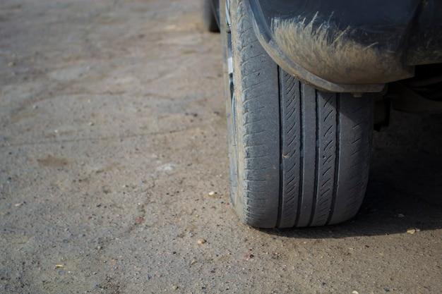 A roda traseira do carro no asfalto substituindo a borracha velha por uma nova