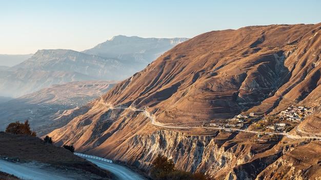 A rodovia contemporânea vazia corre ao longo das encostas rochosas marrons da alta montanha antiga contra o céu azul claro no panorama aéreo ensolarado do dia de outono