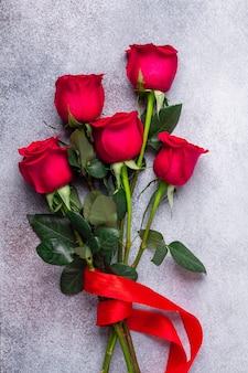 A rosa do vermelho floresce o ramalhete na pedra. dia dos namorados
