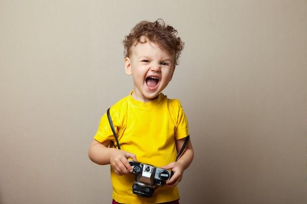 A roupa amarela vestindo do menino 2years velha da criança mantém a câmera isolada, retrato do estúdio das crianças.