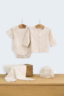 A roupa da criança fêmea da forma (bebê) que pendura na cama de bebê / close-up.