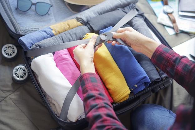 A roupa do bloco da mulher na mala de viagem ensaca na cama, prepara-se para a viagem nova e viaja-se à viagem longa do fim de semana.