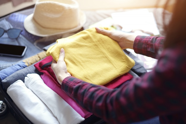 A roupa do bloco da mulher no saco da mala de viagem na cama, prepara-se para a viagem nova.