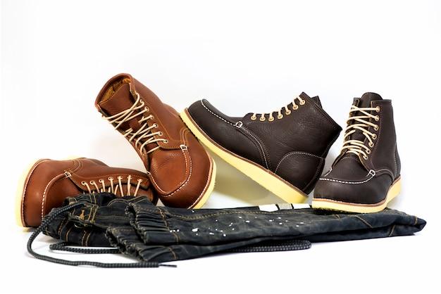 A roupa dos homens ajustou-se com as botas marrons com a calças de ganga isolada em um fundo branco.