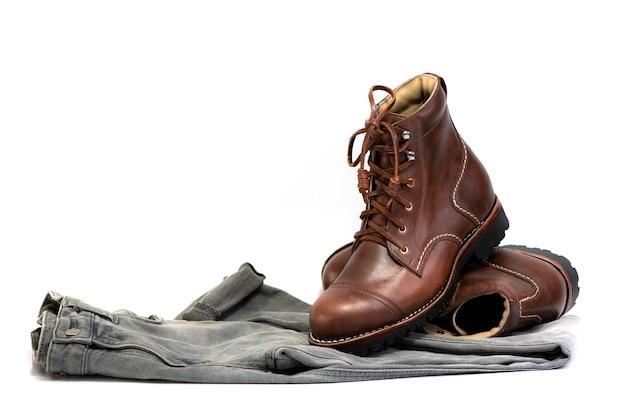 A roupa dos homens ajustou-se com as botas marrons e as calças de brim cinzentas isoladas em um fundo branco.