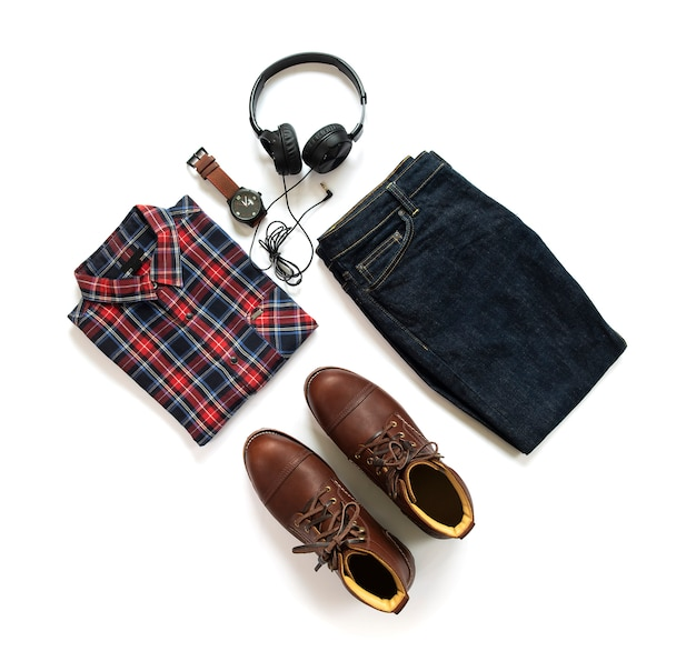 A roupa dos homens ajustou-se com botas marrons, camisa, calças de brim, relógio e fone de ouvido isolados no fundo branco. vista do topo