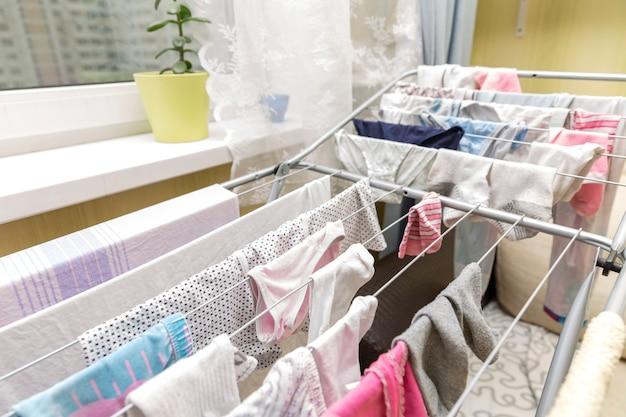 A roupa forrada está pendurada em uma secadora em um apartamento perto da janela.