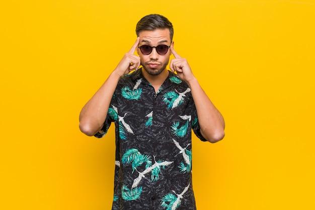 A roupa vestindo do verão do homem filipino novo focalizou em uma tarefa, mantendo os dedos indicadores que apontam a cabeça.