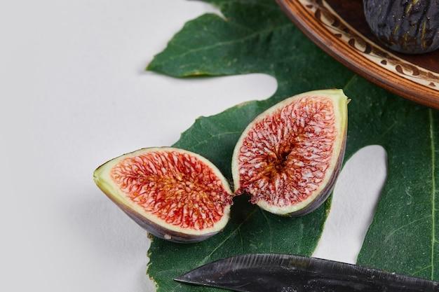 A roxo figos com sementes vermelhas em uma folha verde.