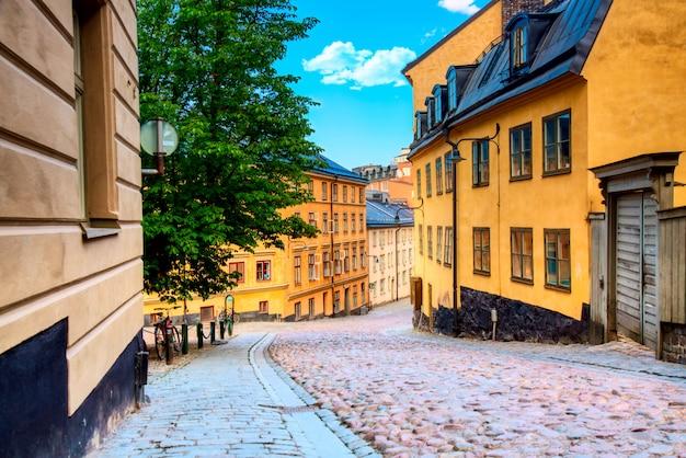A rua de pedrinha estreita bastugatan em sodermalm com casas medievais em estocolmo no dia ensolarado de verão.