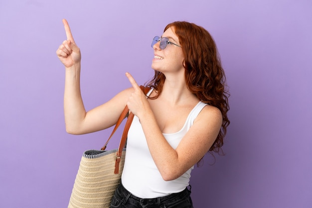 A ruiva adolescente segurando uma bolsa de praia isolada em um fundo roxo apontando com o dedo indicador uma ótima ideia