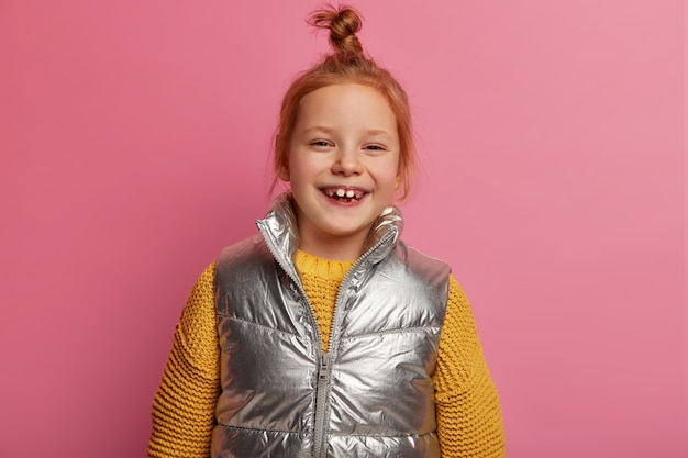 A ruiva positiva ri alegremente, usa suéter e colete de malha quente, gosta de passar o tempo livre com os pais, tem um olhar feliz, sente-se despreocupada, isolada sobre uma parede rosa pastel
