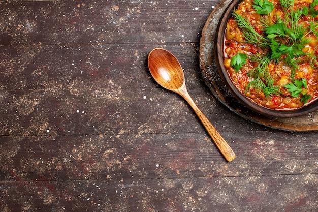 A saborosa refeição cozinhada da vista de cima consiste em vegetais fatiados e verduras em uma refeição marrom de mesa, molho de sopa