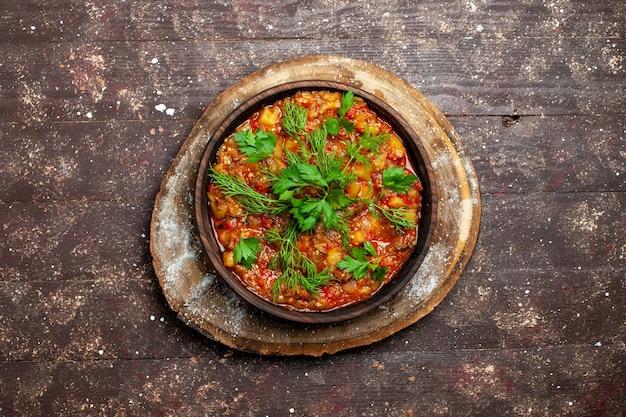 A saborosa refeição cozinhada da vista superior consiste em vegetais fatiados e verduras em uma refeição rústica marrom com molho