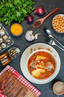 A saborosa sopa de carne, vista de cima, consiste em batatas, carne e feijão em fundo escuro