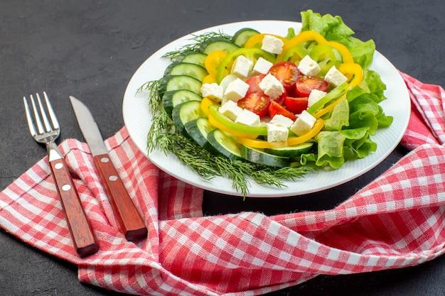 A salada de legumes com vista frontal consiste em fatias de tomate, pepino, pimenta e queijo em fundo escuro
