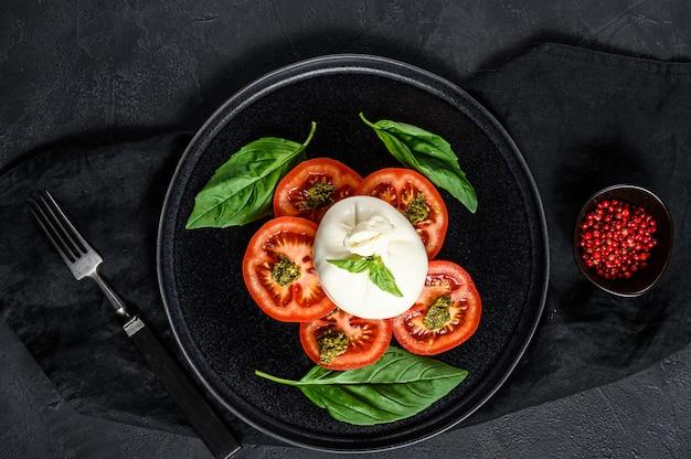 A salada do queijo e dos tomates de burrata serviu na placa preta. vista do topo