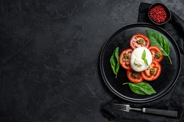 A salada do queijo e dos tomates de burrata serviu na placa preta.