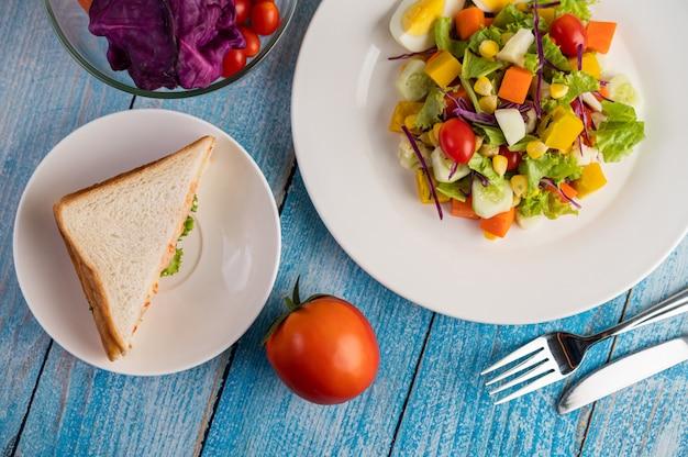 A salada está em um prato branco, com um sanduíche e tomate no chão de madeira azul.