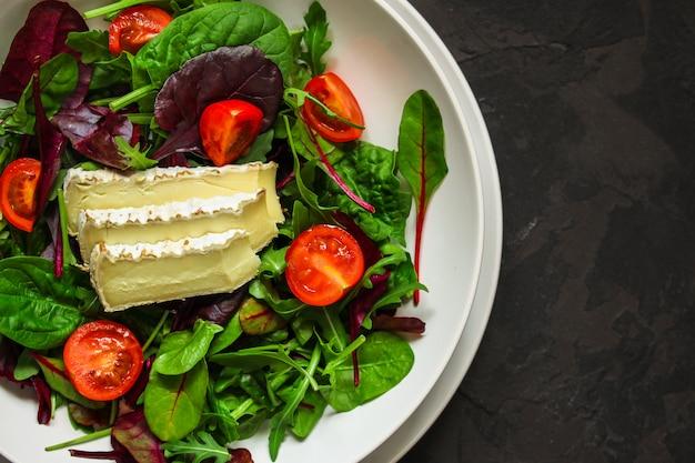 A salada saudável sae em uma placa e em um queijo brancos (os verdes da mistura micro, petisco suculento). fundo de comida