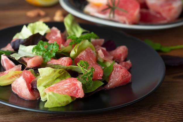 A salada verde saudável com pamplumossa, perde pesa o alimento. plano de dieta. mesa rústica de madeira.