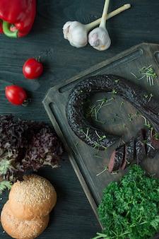 A salsicha de sangue em uma tábua escura é decorada com ervas e legumes frescos. salsicha de sangue. vista de cima. mesa de madeira escura.